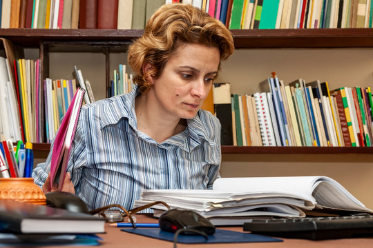 Image of a busy woman teleworking at her desk at the home. Working at home became an important recommendation during the coronavirus outbreak in the beginning of 2020