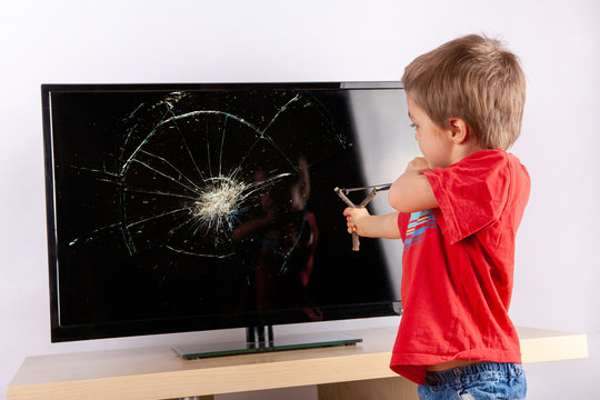 Cute small boy aiming to shattered TV screen with a slingshot.