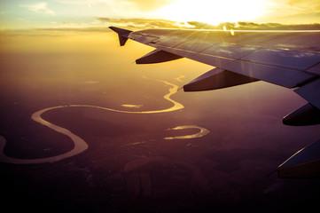 Foto auf Gartenposter Dunkelbraun Cropped Image Of Airplane Flying Above Landscape At Sunset
