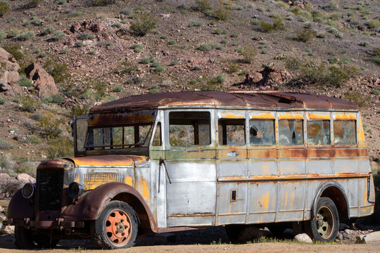 Side view of old vintage school bus abandoned in the desert
