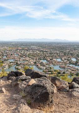 Suburban Arizona skyline above the rooftop, swimming pools, and lake