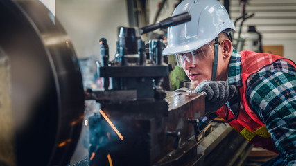 industrial background of caucasian mechanics engineer operating lathe machine for metalwork in metal work factory Fotomurales