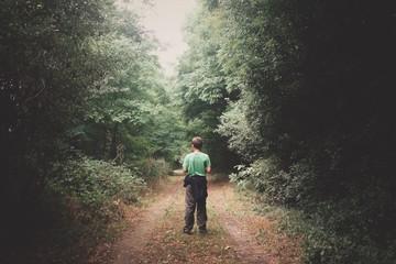 Keuken foto achterwand Weg in bos Rear View Of Boy Standing On Pathway Amidst Trees In Forest