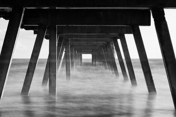 Low Angle View Of Pier Over Sea Against Cloudy Sky