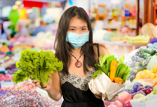 groceries shooping during covid-19 virus quarantine - young beautiful and positive Asian Chinese woman in mask carrying vegetables bag stock up during coronavirus lockdown