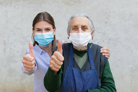 Caregiver with elderly ill woman showing thumbs up