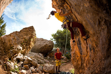 The girl climbs the rock in the shape of an arch, A man is belaying a climbing partner.