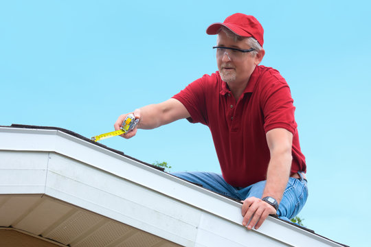 Wind mitigation inspector wearing safety goggles doing inspection on new roof to create a report and risk rating for homeowner to send to their insurance company to receive deductions in policy costs.
