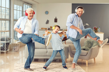 Man with his father and son listening to music at home