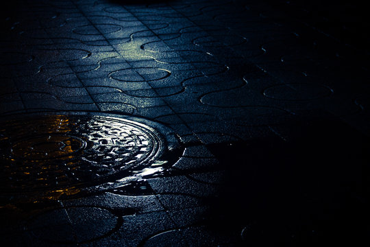 High Angle View Of Manhole On Street At Night