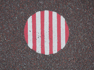 red and white striped circle on a red asphalt road