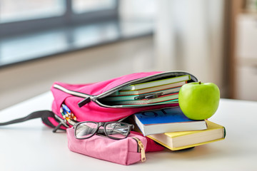 education and learning concept - close up of pink backpack with books and school supplies, green apple on table at home