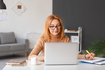 Obraz Mature woman using laptop for online learning at home - fototapety do salonu