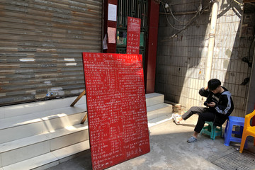 Resident checks his phone next to a sign advertising apartments in the area around Sanyuanli's trading hub in Guangzhou, following an outbreak of the novel coronavirus disease (COVID-19)