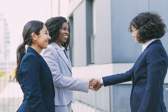 Interracial business partners greeting each other near office building. Business women wearing office suits, shaking hands with each other outside in city. Cooperation concept
