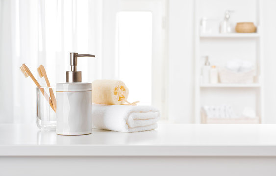 Soap dispenser, toothbrushes and white towel on bathroom counter interior