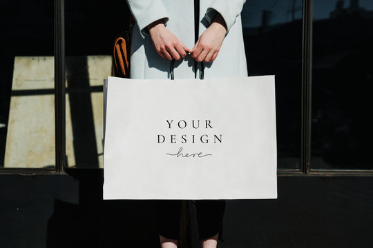 Woman carrying a minimal paper bag