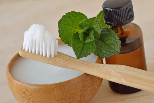 Coconut oil in a bowl with a wooden toothbrush and peppermint essential oil - Homemade natural toothpaste