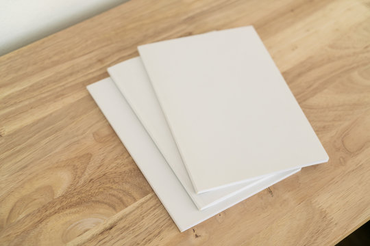 Blank catalog, magazines, book on wood background.