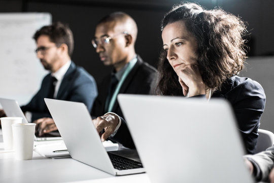 Thoughtful business team working at night in office. Tired woman leaning on hand and looking at laptop screen. Overwork, working late concept