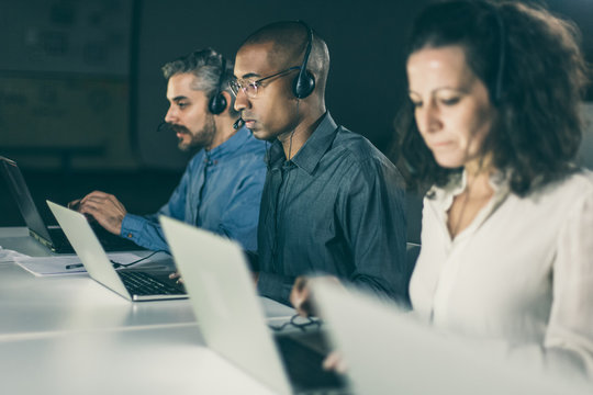 Confident client support team at workplace. Thoughtful call center operators during working process. Call center concept