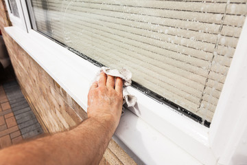 Man wiping down window sill that has been cleaned with soapy water