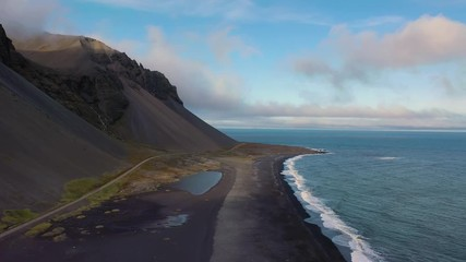 Wall Mural - Flying above a black sand beach near the Eystrahorn Mountains in Iceland