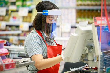 Cashier or supermarket staff in medical protective mask and face shield working at supermarket