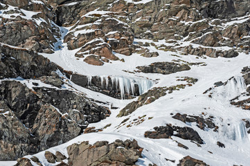 Wall Mural - Rocky alpine mountainside with frozen waterfall