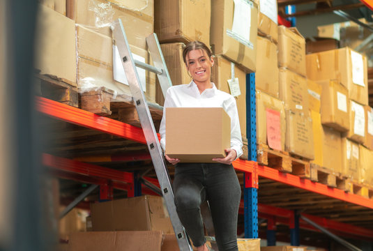 Woman is working in a warehouse with a box in her hand
