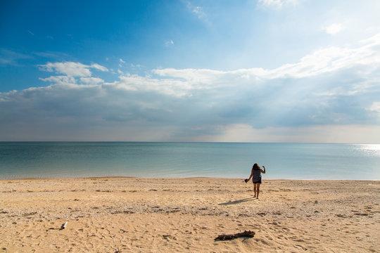 Rear View Of Woman Walking At Sandy Beach
