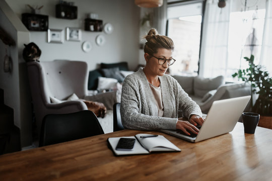 Businesswoman working on laptop computer sitting at home and managing her business via home office during Coronavirus or Covid-19 quarantine
