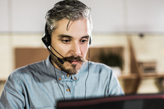 Thoughtful call center operator looking at laptop. Handsome bearded man working with laptop in office. Call center concept