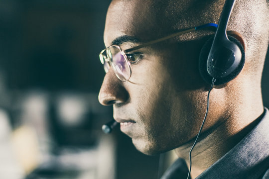 Side view of call center operator. Focused African American man with headset looking at screen. Call center concept
