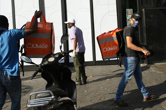 Motorcycle riders carry their delivery bags into a store during a nationwide quarantine due to coronavirus disease (COVID-19) outbreak in Caracas