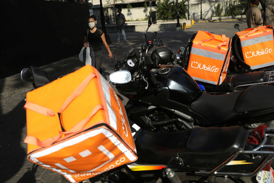 A woman wearing a protective mask walks near delivery bags placed on motorcycles during a nationwide quarantine due to coronavirus disease (COVID-19) outbreak in Caracas