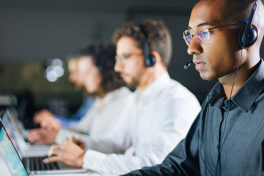Concentrated African American call center operator working. Thoughtful call center operators during working process. Call center concept