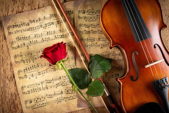 classic retro violin music string instrumt on old music note sheet paper with red rose flower old oak wood wooden background. classical musical romantic valentines day  concept.