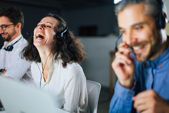 Cheerful mature call center operator laughing at workplace. Smiling curly woman having fun in office. Call center concept