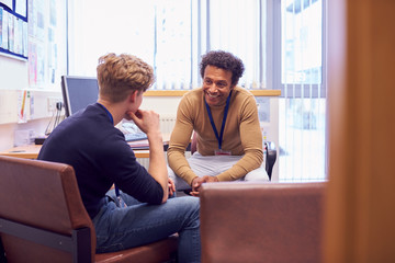 Fototapeta Male College Student Meeting With Campus Counselor Discussing Mental Health Issues obraz