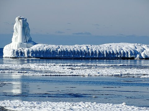 Frozen Lighthouse And Pier By Lake Michigan Against Sky