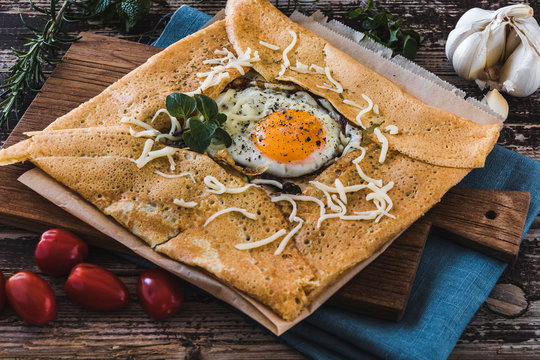 French pancake with fried egg, herbes and cheese on a wooden slat
