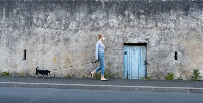 Blonde French woman wearing mask walking dog amid coronavirus outbreak
