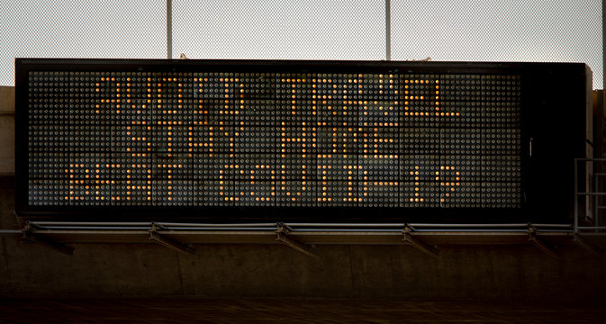 Freeway overpass sign stating Avoid Travel ,Stay Home,Beat COVID-19