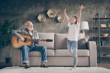 Photo of funny aged old grandpa little pretty granddaughter playing guitar dancing having fun bonding stay home quarantine safety modern interior living room indoors Fotomurales