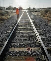Spoed Fotobehang Spoorlijn Rear View Of Person Walking By Railroad Track On Sunny Day