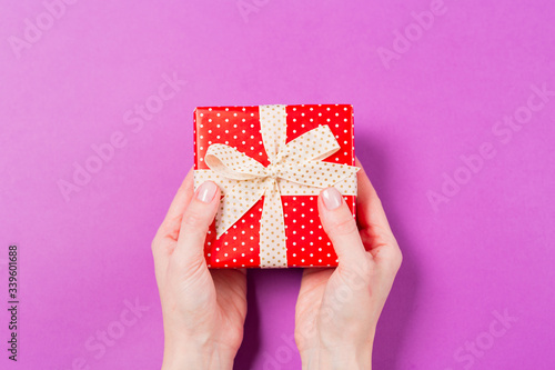 Close-up of woman hands holding gift present box on purple background. Holiday Valentine's Day Mother's Day Wedding concept. Free space. Copy space.