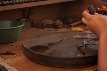 Aluminium Prints Mills .Hands wetting the cigar to sculpt it manual process