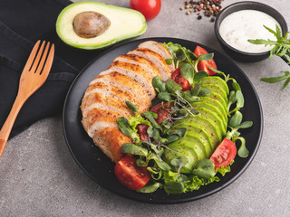 Fototapete - roasted sliced chicken fillet with avocado, tomatoes and herbs on a plate