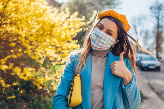 Woman wears reusable mask outdoors during coronavirus covid-19 pandemic. Girl shows thumb up on empty street. Stay safe